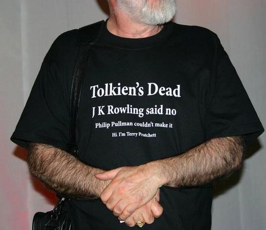 """La maglietta indossata spesso da Pratchett alle convention fantasy: """"Tolkien è morto, la Rowling ha detto di no, Philip Pullman non ce l'ha fatta. Salve, sono Terry Pratchett""""."""