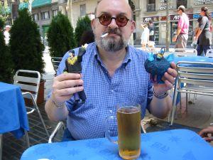 Vic col ricordo più prezioso di Barcellona, due dei tipici pupazzetti spagnoli dedicati ai Beatles. Per l'esattezza, a <i>Yellow Submarine</i>. Da non sottovalutare la presenza della birra.