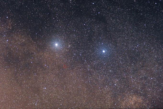 Il sistema ternario di Alpha Centauri. Le due stelle luminose sono Alpha Centauri A e B; la terza stella, molto debole (nel cerchietto rosso) è Alpha Centauri C, nota anche come Proxima Centauri