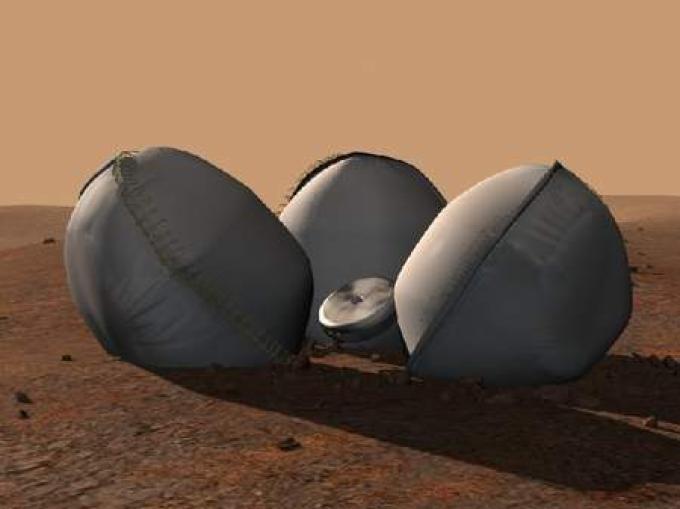 Un'immagine artistica di come avrebbe dovuto essere la configurazione del Beagle 2 e degli air-bag una volta arrestata la sua fase di rmbalzo sulla superficie di Marte.
